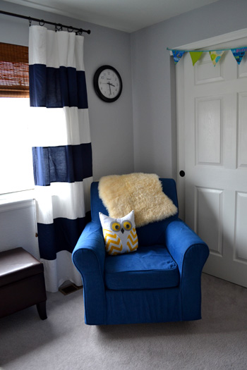 baby boy nursery - navy blue white striped curtains, bamboo blinds, colorful fabric bunting over closet, denim blue slipcover dorel rocking chair, yellow chevron owl pillow, faux leather chocolate ottoman