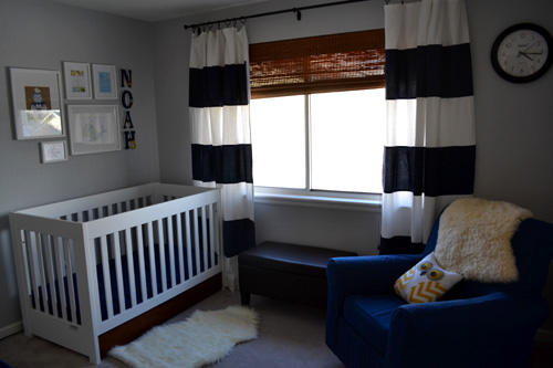 baby boy modern nursery navy blue white striped curtains, white wood crib, art collage over crib, sheepskin flotaki, chocolate ottoman, denim dorel slipcover rocking chair, gray walls